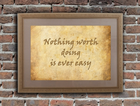 surmount: Old wooden frame with written text on an old wall - Nothing worht doing is ever easy
