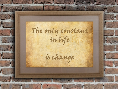 written text: Old wooden frame with written text on an old wall - The only constant in life