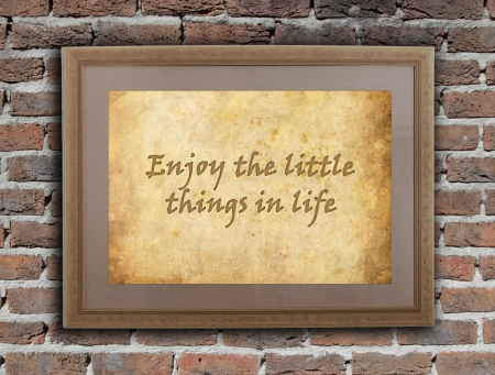 written text: Old wooden frame with written text on an old wall - Enjoy the little things in life