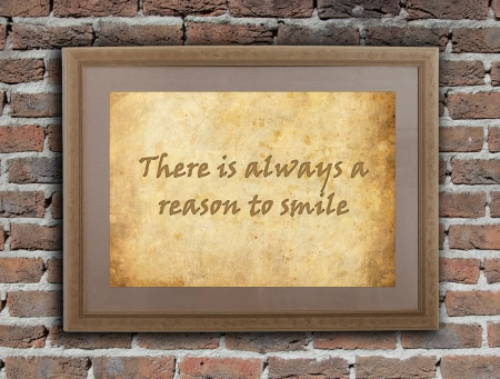 Old wooden frame with written text on an old wall - There is always a reason to smile photo