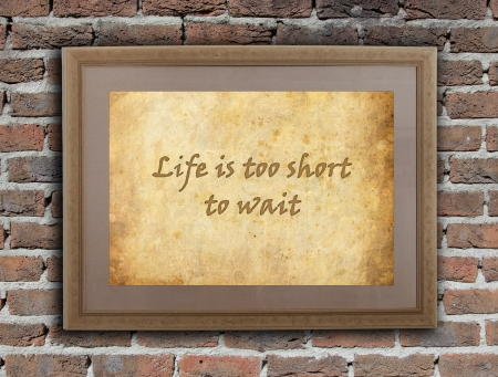 quotations: Old wooden frame with written text on an old wall - Life is too short to wait Stock Photo