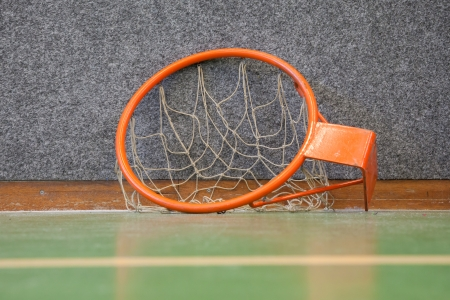 Old basketball hoop with net the floor of a school gym photo