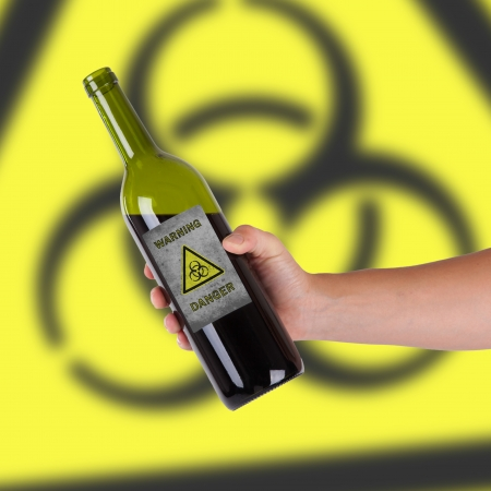 Hand holding a bottle with a warning, biohazard Stock Photo - 23679395