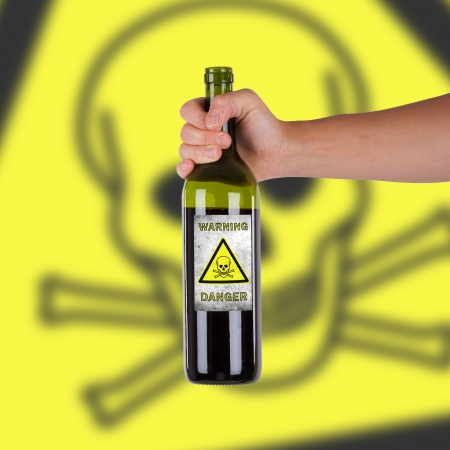 Hand holding a bottle with a warning, poison photo