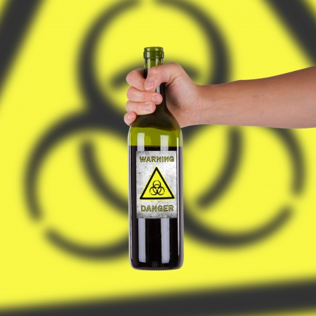 Hand holding a bottle with a warning, biohazard photo