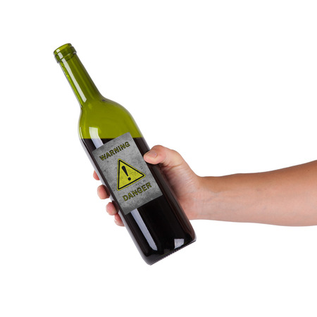 Hand holding a bottle with a warning, danger photo