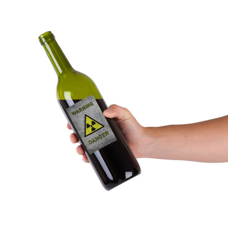 Hand holding a bottle with a warning, radioactive photo