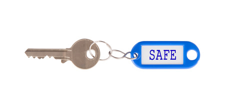 Key with blank label isolated on white background, safe photo
