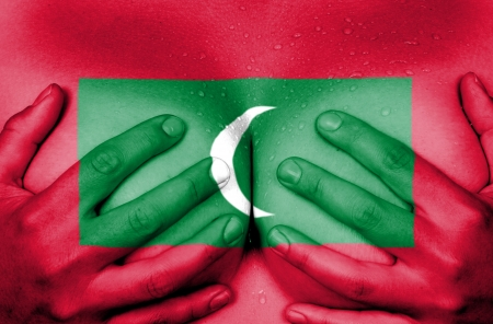 Sweaty upper part of female body, hands covering breasts, flag of Maldives photo