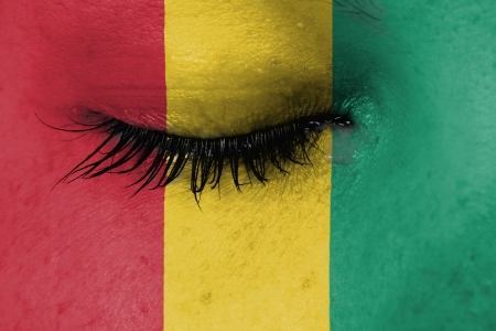 Crying woman, pain and grief concept, flag of Guinea photo