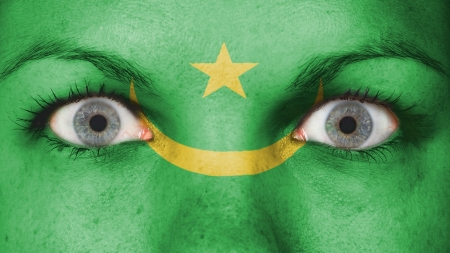 rooting: Close up of eyes. Painted face with flag of Mauritania Stock Photo