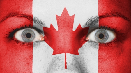 Close up of eyes. Painted face with flag of Canada photo