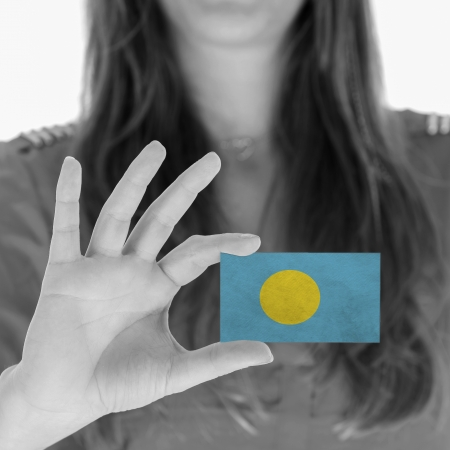 Woman showing a business card, flag of Palau photo