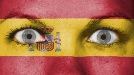 rooting: Close up of eyes. Painted face with flag of Spain Stock Photo