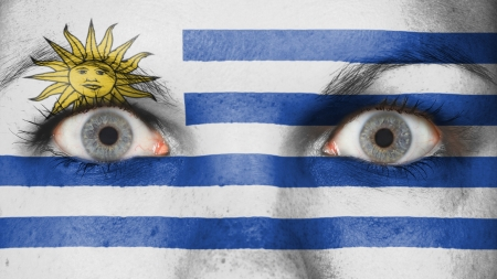 Close up of eyes. Painted face with flag of Uruguay photo