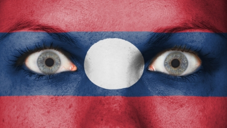 rooting: Close up of eyes. Painted face with flag of Laos Stock Photo