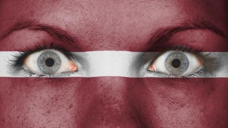latvia girls: Close up of eyes. Painted face with flag of Latvia