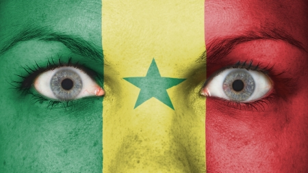 Close up of eyes. Painted face with flag of Senegal photo