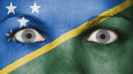 rooting: Close up of eyes. Painted face with flag of The Solomon Islands