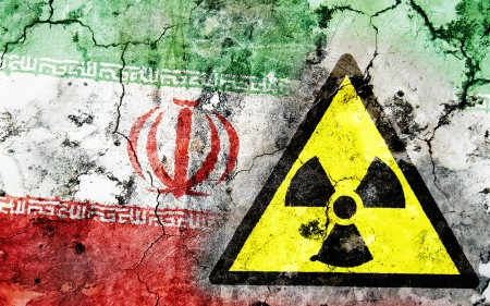 iran: Old cracked wall with radiation warning sign and painted flag, flag of Iran