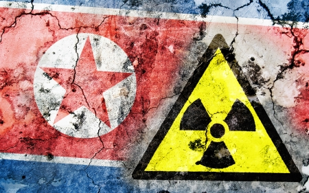Old cracked wall with radiation warning sign and painted flag, flag of Norht Korea Stock Photo