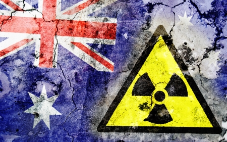 uranium: Old cracked wall with radiation warning sign and painted flag, flag of Australia Stock Photo