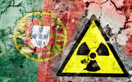 portugese: Old cracked wall with radiation warning sign and painted flag, flag of Portugal Stock Photo