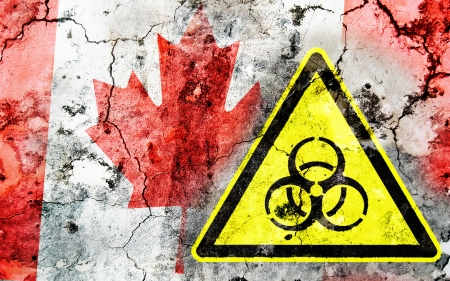 Old cracked wall with biohazard warning sign and painted flag, flag of Canada Stock Photo - 24145315