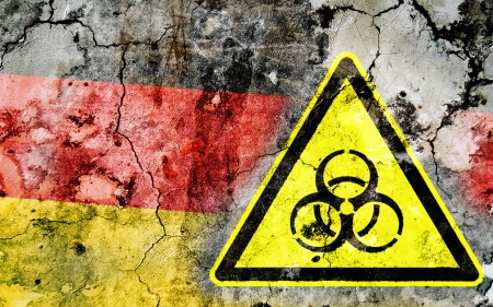 polonium: Old cracked wall with biohazard warning sign and painted flag, flag of Germany