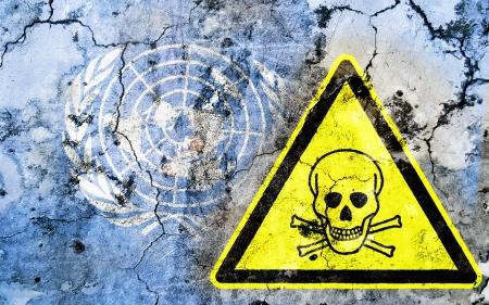 nazioni unite: Vecchia parete incrinata con segnale di avvertimento veleno e bandiera dipinta, la bandiera delle Nazioni Unite