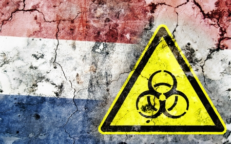 Old cracked wall with biohazard warning sign and painted flag, flag of the Netherlands