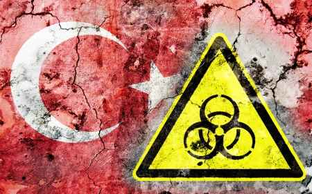 polonium: Old cracked wall with biohazard warning sign and painted flag, flag of Turkey Stock Photo
