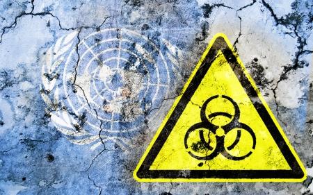 nazioni unite: Vecchia parete incrinata con segnale di avvertimento di rischio biologico e bandiera dipinta, la bandiera delle Nazioni Unite