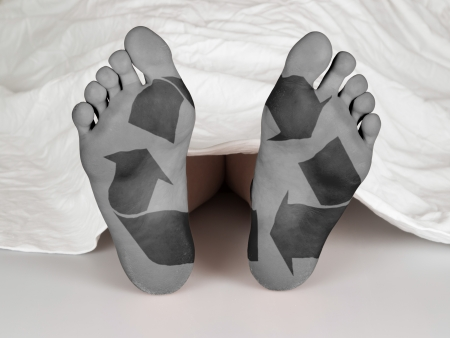 Dead body under a white sheet, concept of sleeping or death, recycle symbol photo
