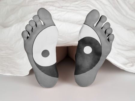 Dead body under a white sheet, concept of sleeping or death, yin yang symbol photo