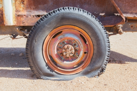 Detail of a vintage abandoned flat car tire on the side of a road, Namibia Stock Photo