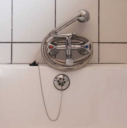 Used chrome metal shower at a bathtub photo