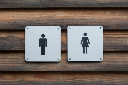 toilet symbol: Man and a lady toilet sign, metal on wood Stock Photo