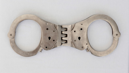 Modern metal handcuffs isolated, used and locked Stock Photo - 25931900