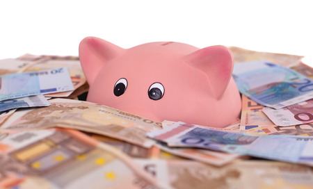 Unique pink ceramic piggy bank drowning in money, isolated on white photo