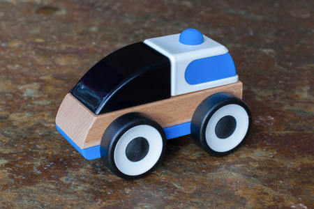 Simple wood and plastic toy police car isolated on a granite floor photo