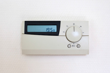 finite: Digital Thermostat set to 19,5 degrees Celsius, isolated on white wall