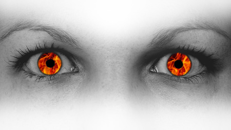 Detail view of female eyes with flames instead of the iris