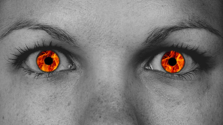 glowing skin: Detail view of female eyes with flames instead of the iris