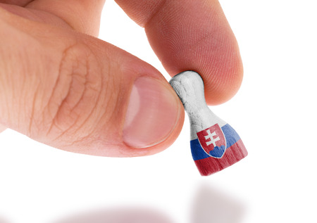 boardgames: Hand holding wooden pawn with a flag painting, selective focus, Slovakia