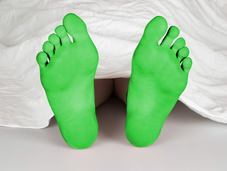 resurrect: Body under a white sheet, suicide, sleeping, murder or natural death, green feet Stock Photo