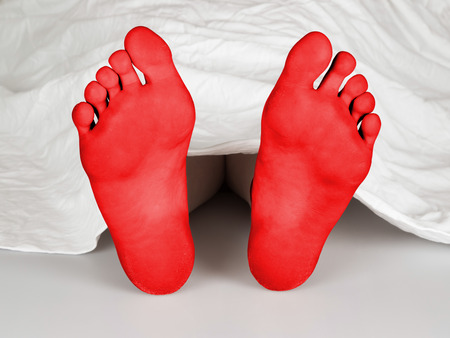 Body under a white sheet, suicide, sleeping, murder or natural death, red feet photo