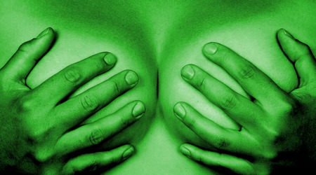 Upper part of female body, hands covering breasts, green photo