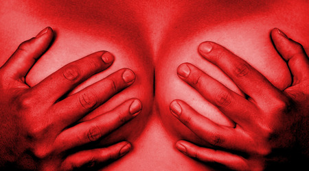 Upper part of female body, hands covering breasts, red photo