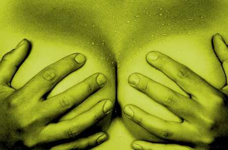Upper part of female body, hands covering breasts, yellow photo